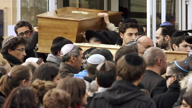 Coffins bearing the four victims are carried from the Ozar Hatorah school on Tuesday, the day after the shooting in Toulouse, in southwestern France. A gunman on a motorbike killed a man and three children outside the Jewish school on Monday.