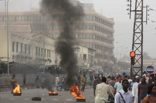 Civilians walk past burning tires lit in support of mutinying soldiers, in Bamako, Mali, on March 21.
