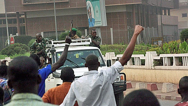 Civilians cheer as mutinous soldiers drive past in Bamako, Mali. Canada announced Saturday it is suspending aid to the Malian government following the military ouster of the West African nation's democratically elected president.
