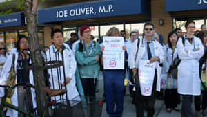 Local physicians gathered outside Conservative minister Joe Oliver's Toronto office and waved placards decrying proposed cuts to health care for refugees and refugee claimants.