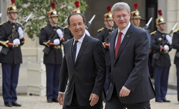 French President Francois Hollande welcomes Prime Minister Stephen Harper upon his arrival at the Elysée Palace in Paris on Thursday.