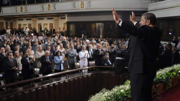 Egyptian President Mohammed Morsi waves to guests after giving an inaugural address at Cairo University in Cairo, Egypt, Saturday.