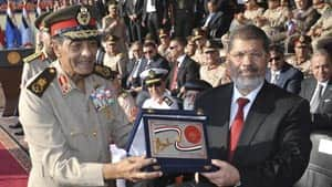 Egyptian President Mohammed Morsi, right, and Field Marshal Gen. Hussein Tantawi, left, pose with the shield of the Armed Forces — the Egyptian military's highest honor, Saturday.