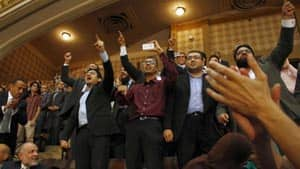 Egyptian activist and former Google executive Wael Ghonim, fourth from right, reacts along with other guests as Egypt's newly inaugurated President Mohammed Morsi appears at Cairo University Saturday.