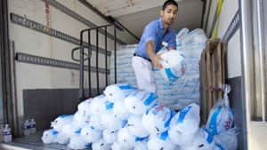 A grocery store employee piles bags of ice for free distribution in Bethesda, Md., on Monday to help community members affected by Friday's storm.
