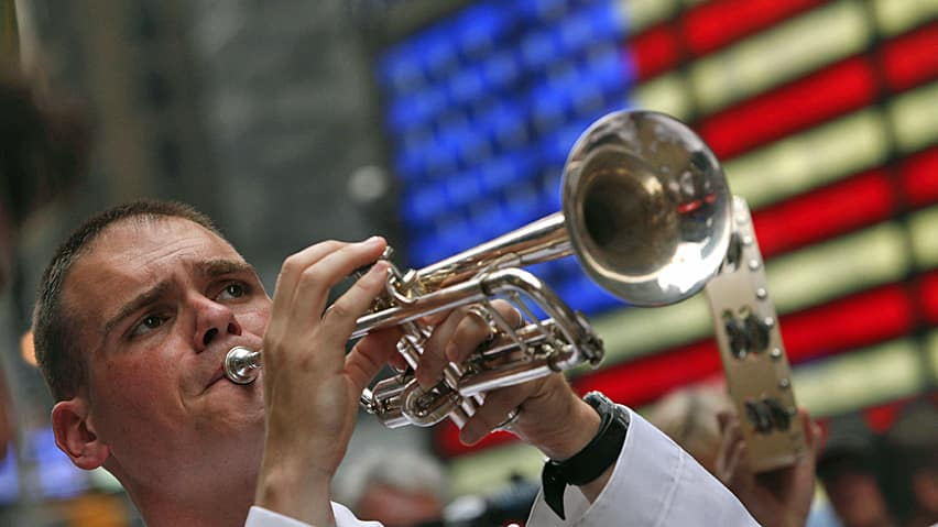 A member of the United States Fleet Forces Brass Band plays his trumpet for a crowd in Times Square.