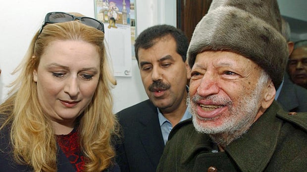The body of late Palestinian leader Yasser Arafat may be exhumed for testing. He is seen at right in this October 2004 photo with his wife Suha (left) prior to his departure from his compound in the West Bank town of Ramallah.