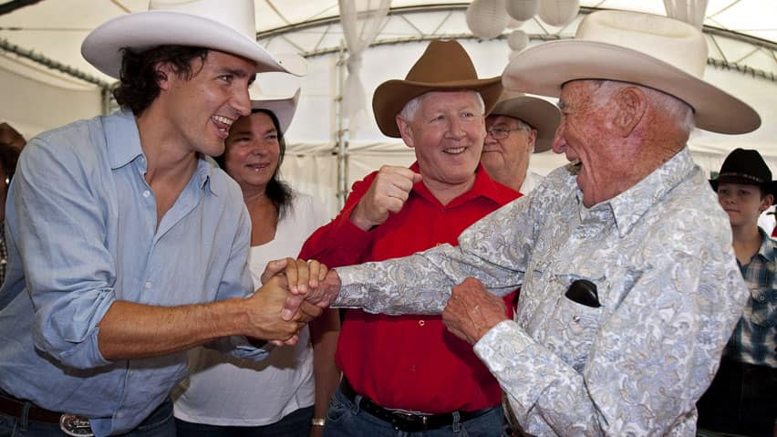 MP Justin Trudeau, left, seen joking with 92-year-old Lyall Curry, right, and Liberal Leader Bob Rae at the Calgary Stampede on Saturday, says he'll announce at the end of summer or start of fall whether he'll run for the party leadership.