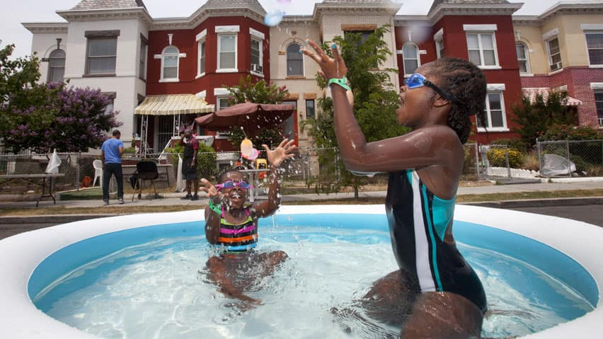 Eight-year-olds Nia Bailey of Washington, left, and Amari Swint of Philadelphia throw water balloons in an inflatable pool during a block party in northwest Washington on Saturday, amid record heat.