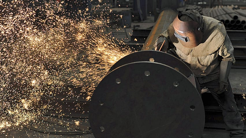 A worker welds a steel product at a plant in China earlier this month. New data Thursday showed the Chinese economy slowed last quarter.