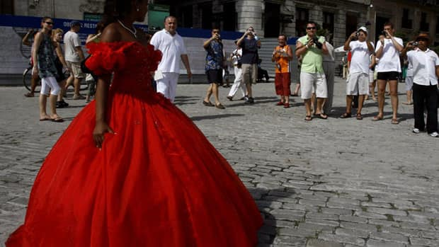 A young woman celebrating her 15th birthday posses for tourists in Old Havana, Cuba. The Cuban government said Tuesday there were 51 new cases of cholera in the capital, but no tourists are known to have contracted the illness.