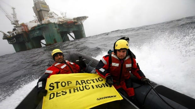 Greenpeace members hold a banner aboard a boat near an oil rig in the Davis Strait, off Greenland's west coast, Friday, June 17, 2011.