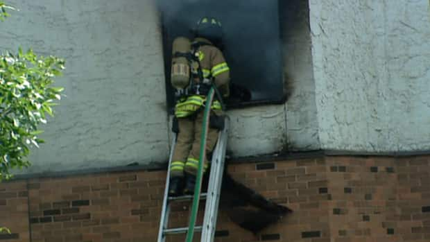 A firefighter battles flames in suite at the Canora Gardens seniors residence Tuesday.