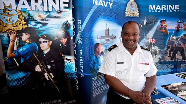 Petty Officer 1st Class Andre Sheppard welcomes visitors at the recruiting booth aboard HMCS Ville de Quebec, in this 2009 photo. The military is missing its recruiting targets for women, visible minorities and aboriginals.