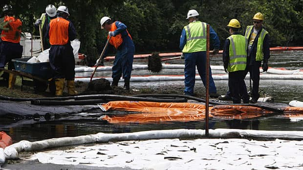In this July 30, 2010 file photo, crews clean up oil from Enbridge's ruptured pipeline near the Kalamazoo River in Michigan. On Wednesday, the Harper government's senior minister in B.C., James Moore, said that Enbridge's behaviour recently has given rise to doubts that are widespread.