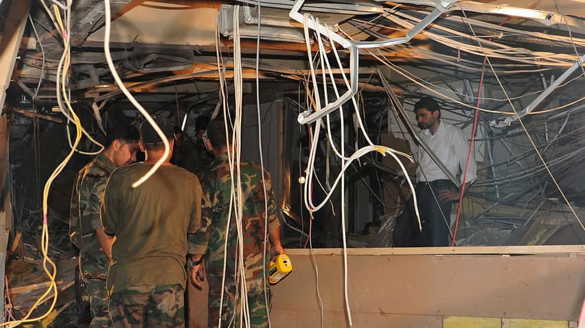 Syrian security forces inspect damages after a blast rocked the headquarters of the Syrian state television in Damascus.