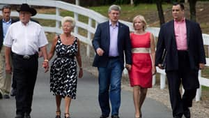 Prime Minister Stephen Harper, centre, and his wife Laureen, walk with Senator Gerry St. Germain, left, and his wife Margaret and Heritage Minister James Moore, right, as they arrive Monday for the annual summer barbecue St. Germain's ranch in Surrey, B.C.