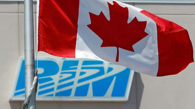 The Canadian flag flies in front of the Research In Motion company logo at one of its buildings in Waterloo, Ont., in June. A judge in California has overturned a jury's order that RIM pay $147.2 million US in a patent lawsuit, the firm says.