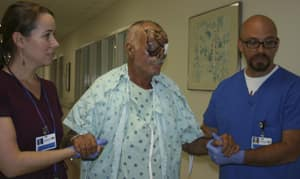 Ronald Poppo, 65, the victim of a gruesome face-eating attack in Miami, is assisted by hospital staff.