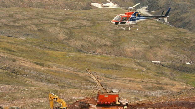 A helicopter passes over excavation equipment at the Mary River exploration camp, the site of a proposed iron mine on northern Baffin Island, in 2006.