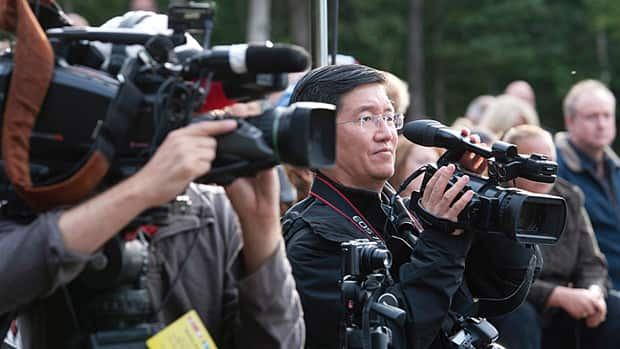 Xinhua Ottawa bureau chief Dacheng Zhang takes video footage during an announcement Wednesday by Stephen Harper in Norman Wells, N.W.T. The representative of the Chinese news agency is among journalists travelling with the prime minister on his annual summer tour of the North.