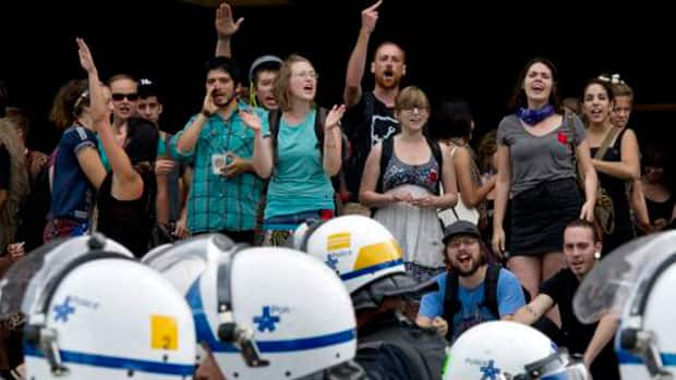 Students yell and gesture at Montreal's police riot squad at a protest at the entrance to a University of Montreal building Monday.