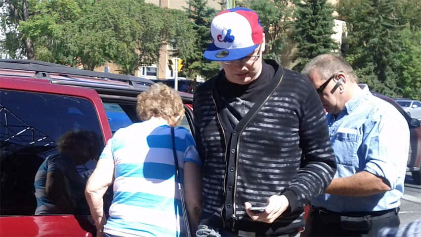 Jason Will, wearing hat, enters Regina's Queen's Bench courthouse Thursday before being sentenced for manslaughter.