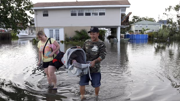 Tony Rodriguez, right, carries his baby daughter Nicole as they and his wife Jodi Clelland leave their flooded home in the aftermath of Hurricane Isaac in Slidell, La., on Friday.