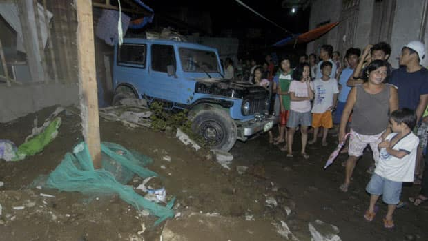 Residents gather at a collapsed house in Cagayan De Oro city, southern Philippines following a 7.6-magnitude earthquake that struck off the Philippines' eastern coast late Friday.