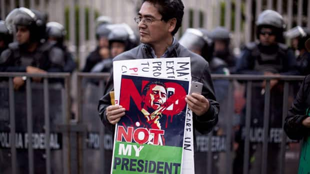A man holds a sign during a protest against Mexico's President-elect Enrique Pena Nieto, of the Institutional Revolutionary Party (PRI), in Mexico City on Friday.
