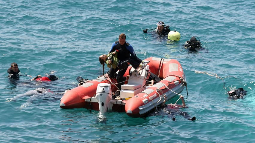A diver from the Turkish sea police carries a girl as other divers look for victims