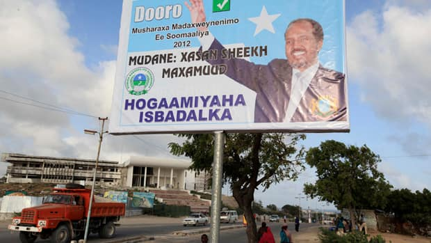 Residents walk past the campaign billboard of Somalia's new president, Hassan Sheikh Mohamud, in Somalia's capital Mogadishu on Monday.
