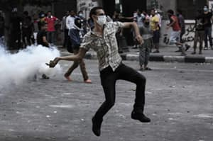 An Egyptian protester throws back a tear gas canister toward riot police, outside the U.S. Embassy in Cairo on Thursday.