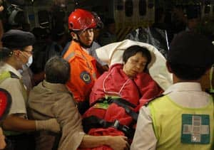 A survivor of Monday's ferry and boat collision in Hong Kong is carried by rescuers onto shore.