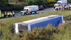 Rescue workers stand by after a bus overturned in a ditch at an exit ramp off Route 80 in Wayne, N.J. on Saturday, Oct. 6, 2012.