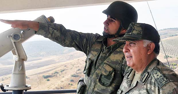 A news agency says Turkish Chief of Staff Gen. Necdet Ozel, right, shown during a tour along the border with Syria in Hatay, Turkey, on Tuesday, has said the country will hit back against ongoing shelling with more force.
