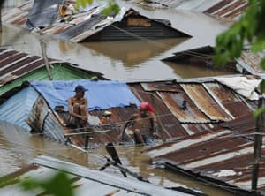 People sit on the rooftop of houses submerged in floodwaters after days of heavy rain in Santo Domingo, Dominican Republic.