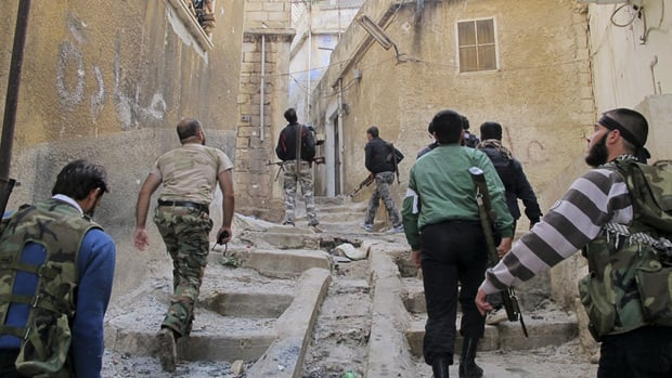 Members of the Free Syrian Army climb up stairs during a patrol in Haram town, Idlib Governorate, on Tuesday.
