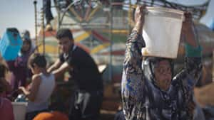 A Syrian woman who fled from the violence in her own village carries a water bucket on her head in Atma, a Syrian village near the Turkish border, on Wednesday.
