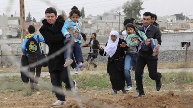 Syrians run as they flee from the Syrian town of Ras al-Ain to Turkish border town of Ceylanpinar, Sanliurfa province on Friday. Around 11,000 Syrian refugees fled into Turkey, Jordan and Lebanon in the past 24 hours, the UN refugee agency said on Friday.