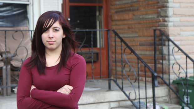 Jordan Fancey stands in front of her neighbours' east Hamilton home, where a fire broke out early Tuesday morning.