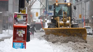 A snowplow in downtown Toronto Thursday pushes aside wet overnight snow, the city's first major snowfall of 2012. The storm moved east to Montreal, where it was set to break a record.