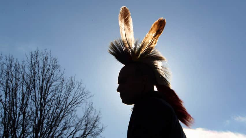 Alex Rogers wears a grass dance headdress near a railway blockade line in Sarnia, Ont. last month. The Idle No More movement has spread as far afield as Texas and New Zealand.