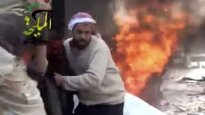 This citizen journalism image taken from video provided by Shaam News Network shows a wounded man being pulled from the site of a Syrian government airstrike on a gas station in the eastern Damascus suburb of Mleiha on Wednesday.