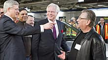 Prime Minister Stephen Harper, left, is greeted by CAW President Ken Lewenza, right, and Oakville MP Terence Young at the Ford plant in Oakville Ont., where Harper announced the renewal of the automotive Innovation Fund Friday.