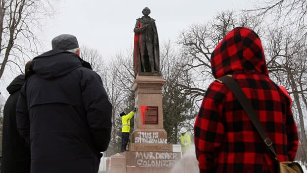 City of Kingston employees remove graffiti on the statue of Sir John A. Macdonald, Canada's first prime minister, in City Park on Friday.