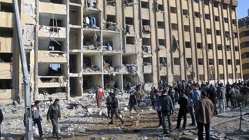 Syrian security personnel and civilians gather at the site where two explosions rocked the University of Aleppo in Syria's second largest city on Tuesday.