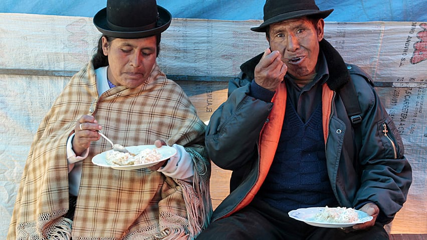 An Aymara couple eat food named 'Peske' cooked with quinoa grains in Bolivia. Western demand for the food has caused prices to soar.