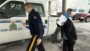Joyce Neyelle of Deline, N.W.T., is led by RCMP into the Yellowknife courthouse on Friday. She was sentenced to five and a half months in jail for assaulting two elders and a police officer.