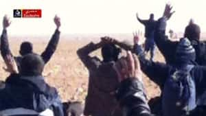 In this image made from video, individuals believed to be hostages kneel in the sand with their hands in the air at an unknown location in Algeria.